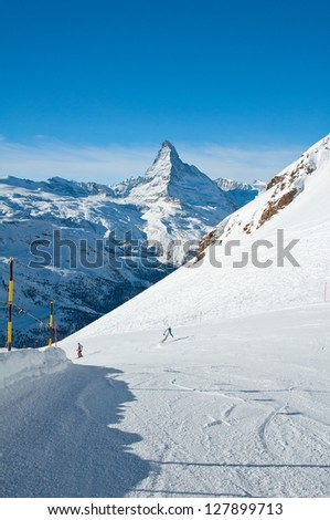 Skier and snowboarder on the slope with Matterhorn in background - stock photo