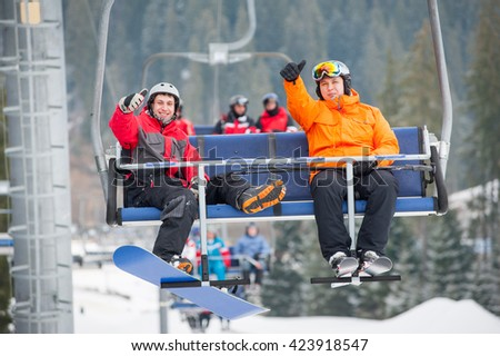Skier and snowboarder riding up to the top of the mountain on ski lift and showing thumbs up gestures of good class, with an astonishing view nature. Close-up - stock photo