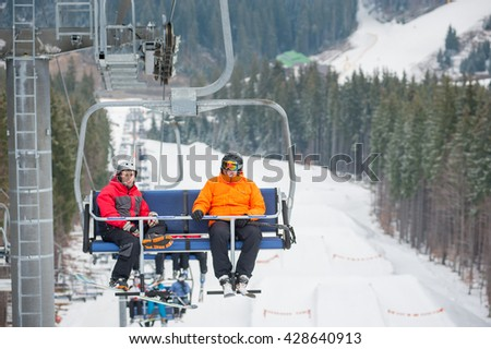 Skier and snowboarder riding up to the top of the mountain on ski lift, with beautiful view nature - stock photo
