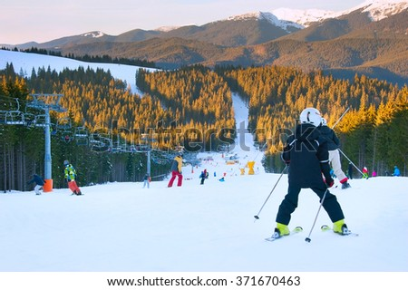 Skier and snowboarders on a mountains slope at sunset - stock photo