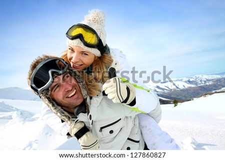 Skier at the mountain giving piggyback ride to girlfriend - stock photo