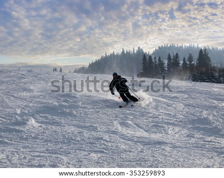 Skier descend down the slope of the ski piste on the background of forest and sky with clouds  - stock photo