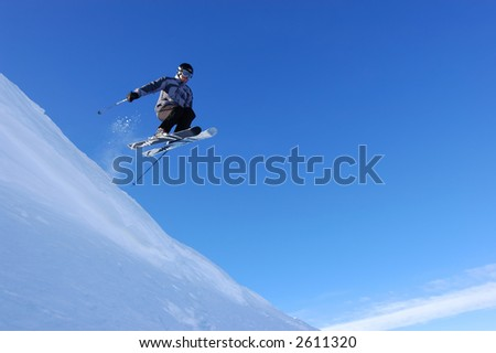 Skier flying off a cornice - stock photo