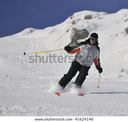 skier free ride downhill at winter season on beautiful sunny day - stock photo