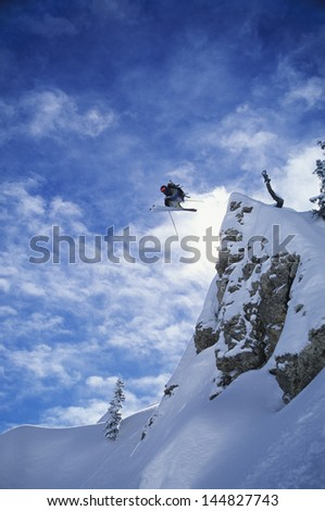 Skier jumping from mountain ledge against clear sky - stock photo