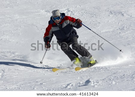skier moving down on the snow slope - stock photo
