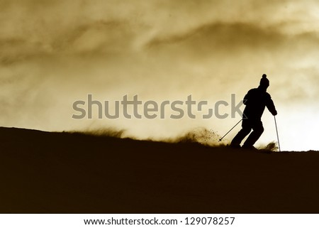 Skier on a slope at sunset - stock photo