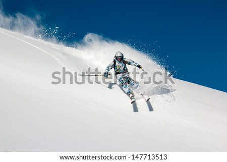 Skier on a steep mountain slope. In turn raises the snow dust. - stock photo