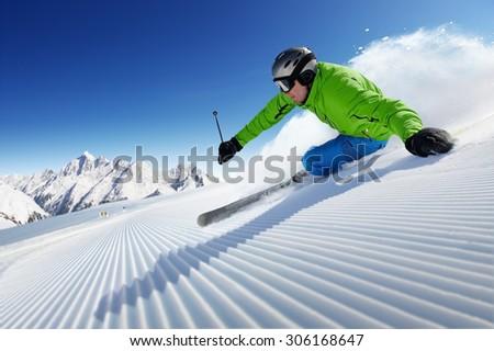 Skier on piste in high mountains. Ski photo. Skiing man. Ski theme. Ski background. Skiing photo. Skiing fun. Enjoying ski. Fast Skiing. Ski at winter. Alpen Skiing. Ski photograph. - stock photo