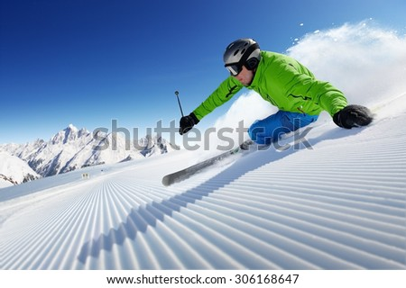 Skier on piste in high mountains with beautiful clear weather and prepared piste - stock photo