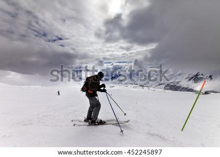 Skier on ski slope before storm. Caucasus Mountains. Georgia, ski resort Gudauri. Wide angle view. - stock photo