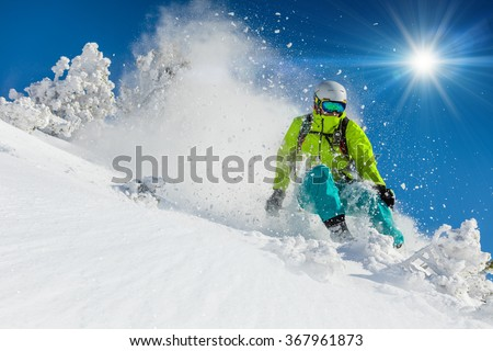 Skier skiing downhill during sunny day in high mountains - stock photo