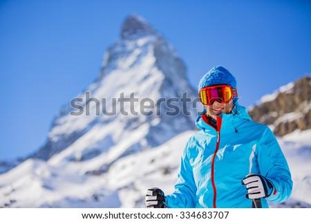 Skier woman with view of Matterhorn on a clear sunny day - Zermatt, Switzerland - stock photo
