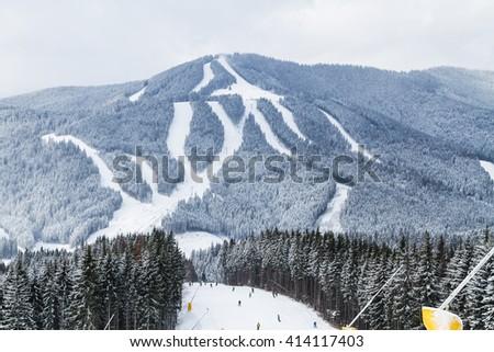 Skiers and snowboarders enjoying on slopes of ski resort Bukovel, Ukraine.   - stock photo