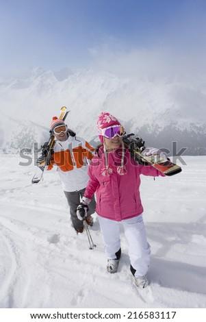 Skiers carrying skis across ski slope - stock photo