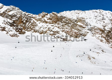 Skiers exit the tunnel connecting the two large glaciers at the Austrian ski resort Soelden. - stock photo