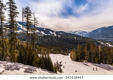 Skiers go down the ski slopes with the Canadian Rocky Mountains in the background on a bright sunny day. - stock photo