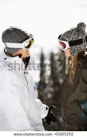Skiers on a ski slope wearing ski goggles and hats and smiling at each other. Vertical shot. - stock photo
