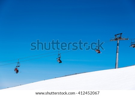 skiers on a skiing lift in the alps - stock photo
