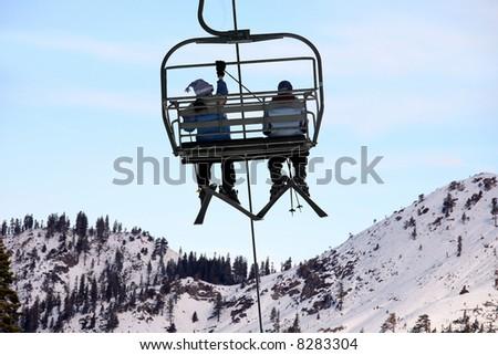 Skiers on chairlift at Lake Tahoe ski resort. - stock photo