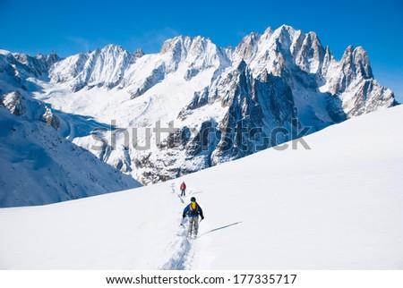 skiers on ski run - stock photo