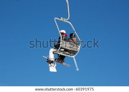 Skiers on the ski lift (Amden, Switzerland) - stock photo