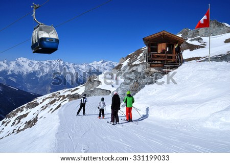 Skiers on the ski slope in Swiss Alps in sunny day. Small wooden house with red swiss flag near by. Blue cable car above and mountains behind, skiing resort Thyon 2000, Switzerland. - stock photo