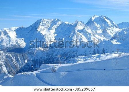 skiers on the slope, the cableway in the Alpine mountains, blue landscape, courshevel region, three valleys, France - stock photo