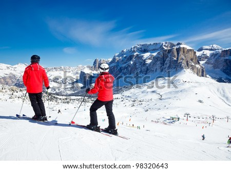 Skiers overlooking the piste at Val Di Fassa ski resort in Italy - stock photo
