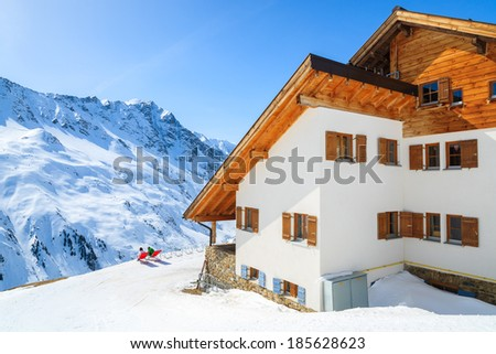 Skiers rest on sunchairs in front of mountain refuge hut with peaks of Austrian Alps in background, Riffelsee ski resort in Pitztal valley  - stock photo