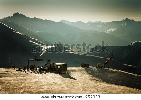 Skiers waiting at the lift in the middle of the Swiss Alps -- gorgeous backdrop. - stock photo