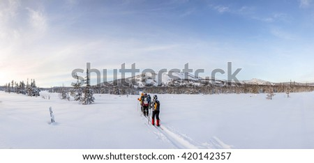 Skiers walking on snow covered mountain ranges, Ural, Russia - stock photo