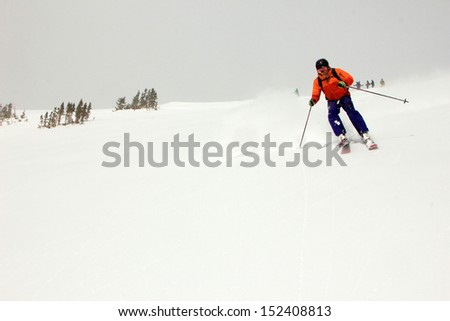Skiers watch as a man skis an extreme slope, Utah, USA. - stock photo