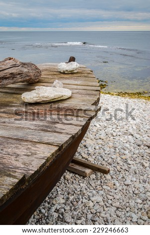Skiff boat on stone beach by the ocean with stones on boat cover - stock photo