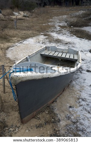 Skiff drawn up on icy shore  - stock photo