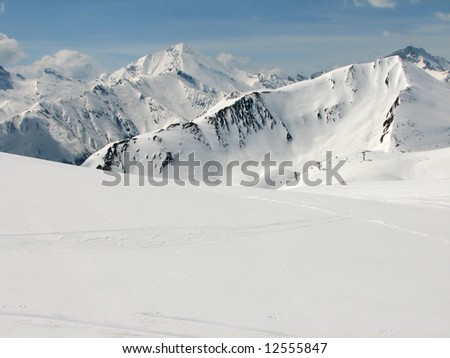 Skiing area in the Alps with high mountains and a chair lift in the back - stock photo