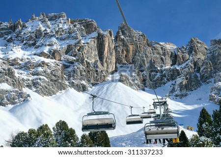 Skiing on the dolomites, Cabs for skiers above the horizon in the background mountains. Val di Fiemme, Italy. - stock photo