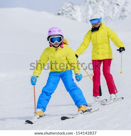 Skiing, skiers on ski run - child skiing downhill, ski lesson - stock photo