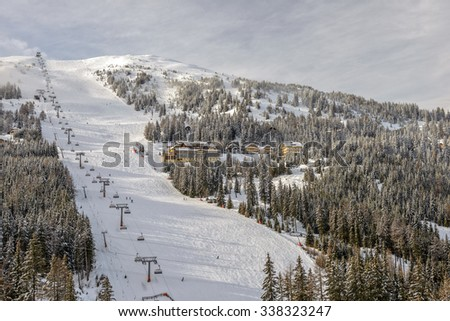 Skiing slopes with chairlift on ski resort in Austrian Alps - stock photo