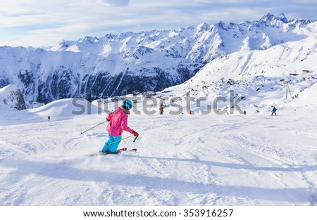 Skiing, winter, child - portrait of young skier girl in helmet and goggles in winter resort - stock photo