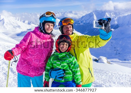Skiing, winter fun - happy family taking picture at the ski slope - stock photo