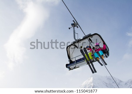 Skiing, winter - skiers on ski lift - stock photo