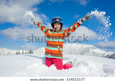 Skiing, winter, teenage girl - young skier girl playing in snow in winter resort - stock photo