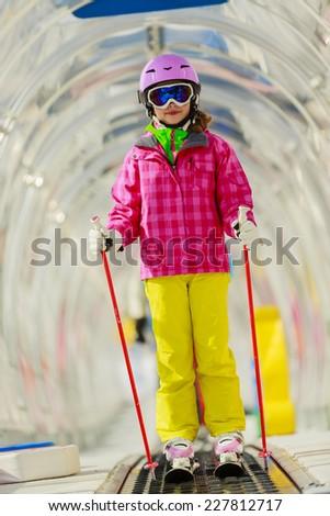 Skiing, young skier on ski lift, ski moving walkway - stock photo