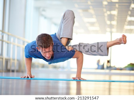 Skilled guy doing physical exercise in gym - stock photo