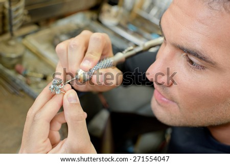 Skilled jeweller repairing a ring - stock photo