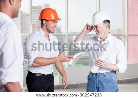 Skilled old architect and young foreman are ready to work together. The worker is proposing to architect handshake with joy. The man is looking at him and smiling - stock photo