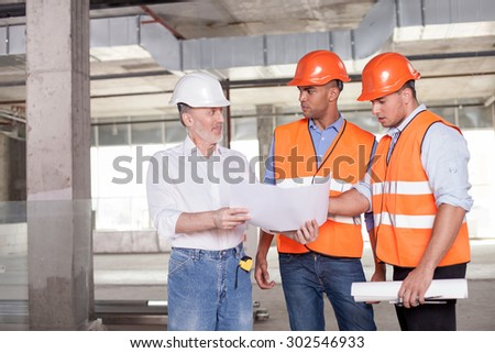 Skilled old architect is explaining to workers his ideas about a project with aspirations. He is smiling. The men are looking at blueprint with surprise. Copy space in left side - stock photo