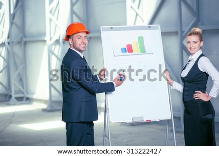 Skilled two engineers are standing near a board with a blueprint. The man is explaining to his colleague the concepts of building and writing down his ideas. They are smiling - stock photo