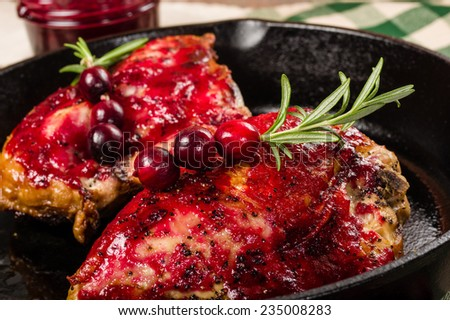 Skillet of cast iron with two glazed chicken breasts - stock photo